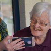 Image of older woman looking at phone, in relation to digital social care